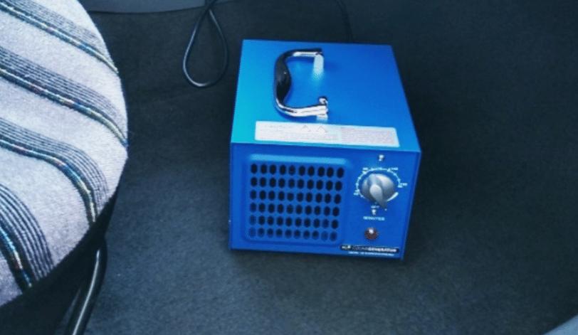 Générateur ozone de 7g de couleur bleue posé sur le sol du véhicule pour la désinfection